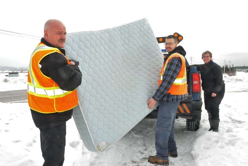 Michelle Cormier, right, chair for Aunt Jean's Place Inc., looks on as Town of Stephenville Public Works Department employees, from left, Tony March and Wayde Smith, load a mattress donated by Hotel Stephenville. The shelter provides temporary housing for those in need. FRANK GALE/THE WESTERN STAR