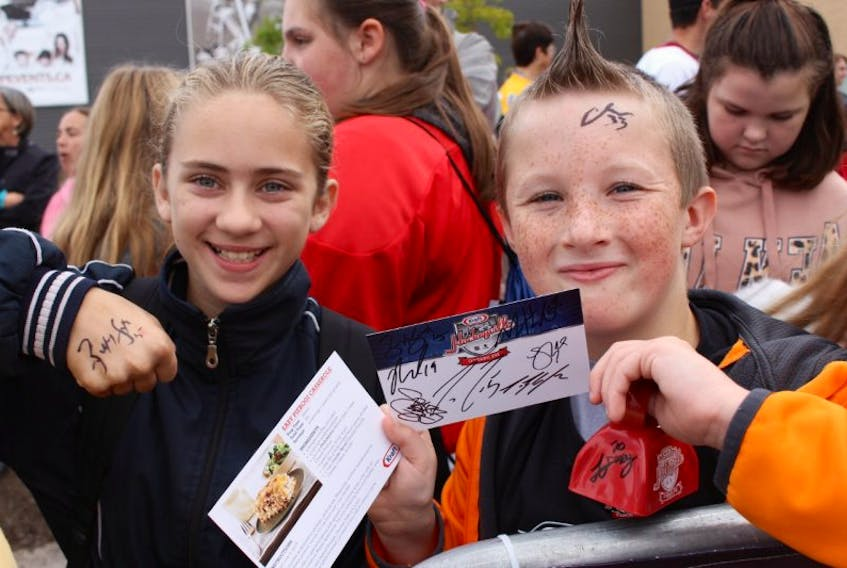 Alesha Bernard, left, and Colby Smith display the autographs they gathered as NHL players entered Credit Union Place for Kraft Hockeyville.