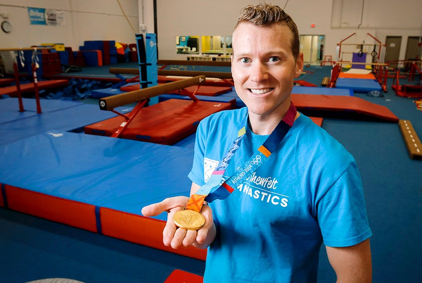Kyle Shewfelt shows his Olympic gold medal at his gymnastics facility in southeast Calgary, Alta., on Thursday, Aug. 21, 2014.
