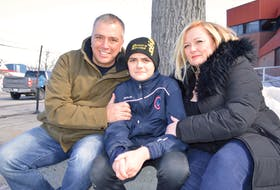 Chase MacNeil, 14, centre, who was violently attacked at Riverview High School Wednesday in an incident caught on video, relaxes in Sydney on Friday with his parents, father Craig MacNeil, of Howie Centre and mother Tricia MacNeil of Westmount. Chase said he's still a little upset over the ordeal and is still sore and although doesn't know yet when he'll be returning to school, doesn't feel he'll be scared to go back as he knows there's a lot of support out there for him and it's making him feel good. Sharon Montgomery-Dupe/Cape Breton Post