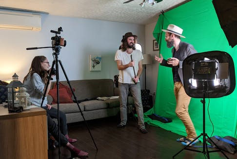 """Brendan Henry, right, chats with Andrew Waite, centre, and wife Brianna Henry, left, while shooting Waite's music video """"Ain't Goin' out Like That."""""""