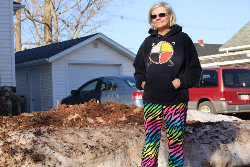 Kim Lyon stands next to the pile of dirty snow on her garden. The snow was eventually removed on March 25, after most of it had melted. She had been asking the city to clean it up for a month prior, and worries how much damage her soil sustained in that time.