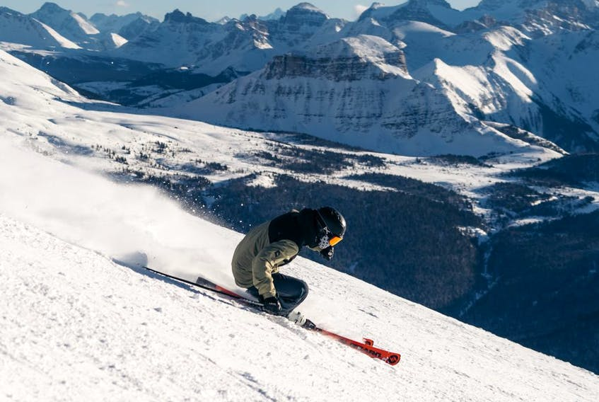 A skier makes makes a turn with Mount Assiniboine in the background at Banff's Sunshine Village.
