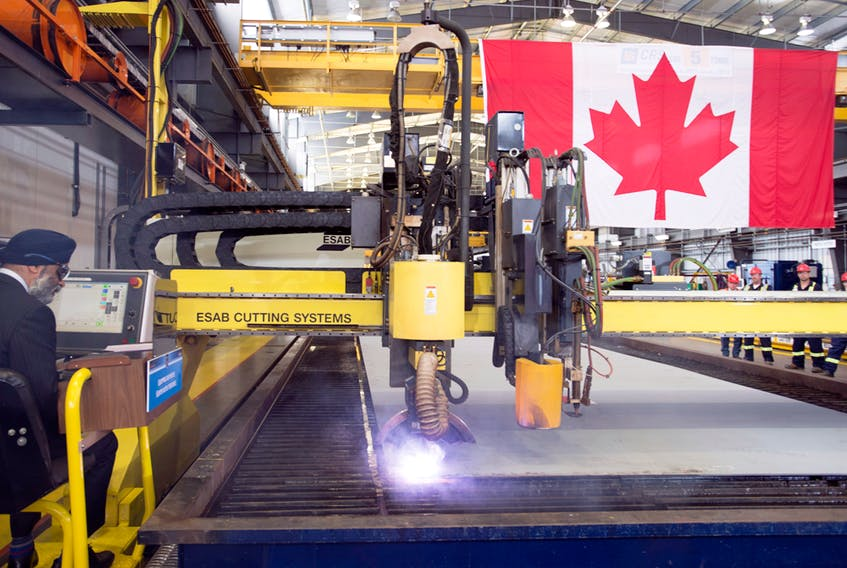 Defence Minister Harjit Sajjan, left, cuts steel for the first of two Joint Support Ships for Canada's Navy at the Seaspan Shipyards in Vancouver, June, 15, 2018.