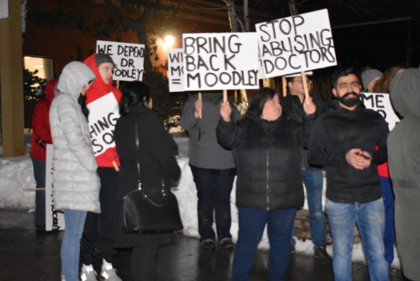 A group of supporters of Dr. Manivasan Moodley attend a rally outside of the Cape Breton Regional Hospital in Sydney on Thursday. About 50 people attended the rally, despite bitter cold winds. NIKKI SULLIVAN/CAPE BRETON POST