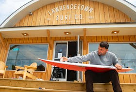 Nico Manos, co-owner of Lawrencetown Surf Co., waxes a board in front of his new surf shop on Monday, July 13, 2020. Ryan Taplin - The Chronicle Herald