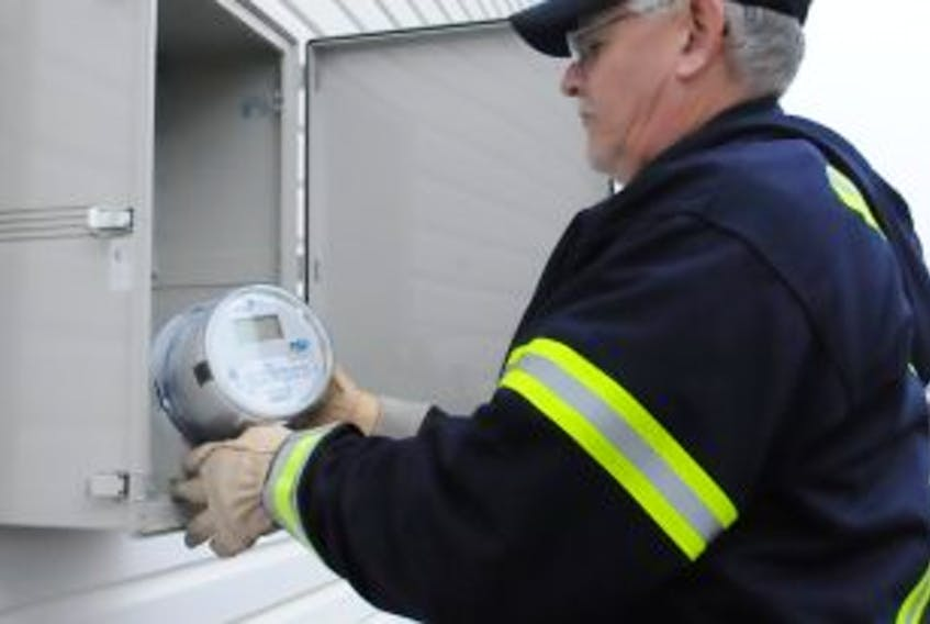['Summerside Electric employee Larry Blacquiere installs a smart metre on a city building. The Smart Grid technology is cited as one of the reasons why Summerside received first place for sustainability in Atlantic Business Magazine's 2012 Corporate Social Responsibility awards.']