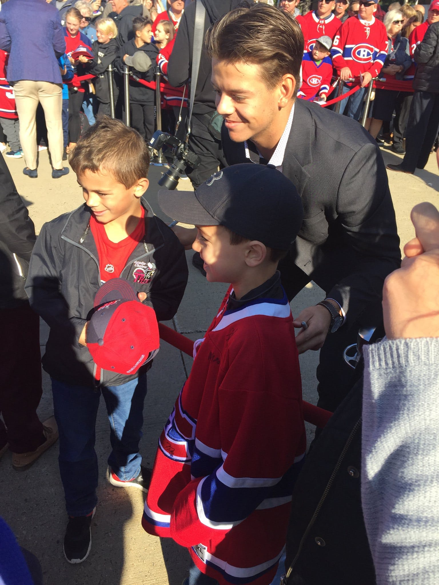 Montreal Canadiens Jesperi Kotkaniemi poses for photo with young fans in Bathurst.