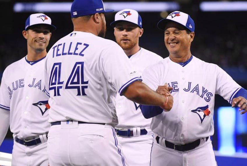 Blue Jays Rowdy Tellez (left) is greeted by manager Charlie Montoyo prior to the game on Thursday.