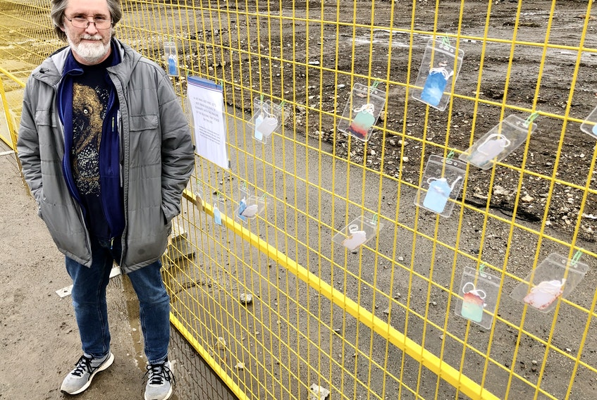 Artist Greg Davies stands next to an installation he erected on Friday in memory of the homeless person who was found dead in a derelict building in Sydney. The building is now demolished. NICOLE SULLIVAN/CAPE BRETON POST