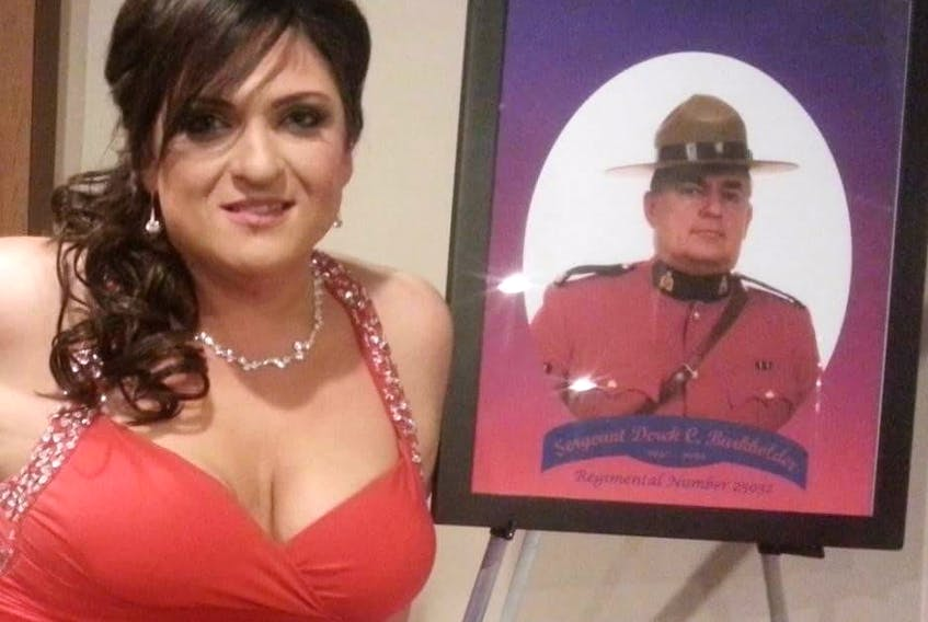 Tanya Burkholder poses with a photo of her father, RCMP Sgt. Derek Burkholder, at a ceremony to recognize his public service. Sgt. Burkholder was killed on a police call in 1996.