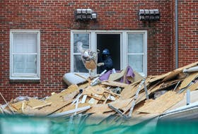 A contractor throws garbage onto a pile, as demolition preparation continues at Ardmore Hall in January.