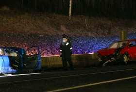 FOR NEWS STANDALONE: A Halifax regional police officer examines the scene of a 2 vehicle accident on Highway 11, near Exit 8 in Dartmouth Saturday February 7, 2021. STILL AWAITING RELEASE....IT APPEARS RED VEHICLE TRAVELED IN WRONG LANE.  TIM KROCHAK PHOTO