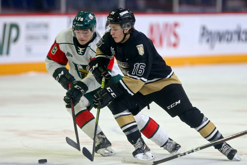 Halifax Mooseheads Liam Peyton tries to steal the puck from Charlottetown Islanders Patrick Guay during QMJHL action in Halifax Sunday March 14, 2021.  TIM KROCHAK PHOTO