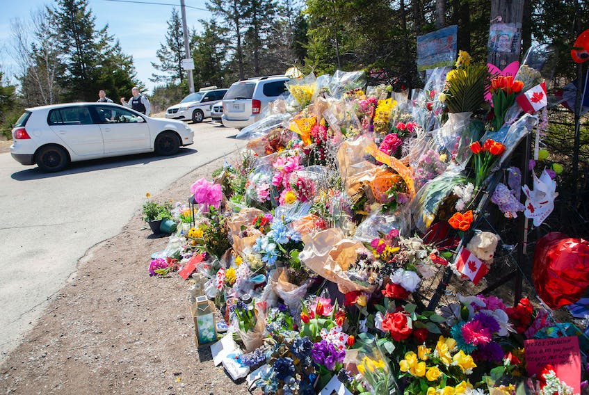 RCMP officers speak with a visitor near the large memorial in memory of the victims from the mass shooting seen at Portapique Beach Road in Portapique, N.S., on Thursday, April 30, 2020.