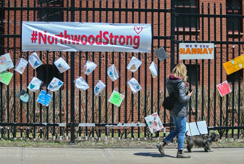 A woman walks past messages of support for residents and staff at Northwood placed across the street of the retirement and care facility in Halifax Wednesday May 6, 2020.