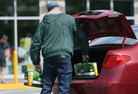 A man places a couple of cases of beer into his trunk, after leaving an NSLC outlet in Dartmouth, Wednesday, May 27, 2020.