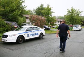 """FOR NEWS STORY: A Halifax regional police officer surveys the street following an incident on Renfrew Street in Dartmouth  Sunday July 12, 2020.  One person was taken to hospital. FROM POLICE RELEASE: """"At approximately 8:20 a.m. Halifax Regional Police patrol members responded to a report of a male who had been stabbed on the roadway on Renfrew Street in Dartmouth.  Officers located an 18-year-old male suffering from a stab wound. The male was transported to the hospital with serious injuries""""  TIM KROCHAK/ The Chronicle Herald"""