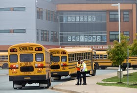 Staff keep track of the dozens of buses arriving with students, for first day of classes at Charles P. Allen High School in Bedford, Tuesday September8, 2020.