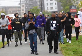 About 50 people turned out this morning to walk Demario Chambers, left, to school at Charles P. Allan, Tuesday, Sept. 8, 2020. The walk was organized to give support to the teen, who was wrestled to the ground during an arrest by police at a Bedford Mall last spring.