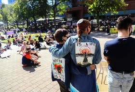 Julia Sampson and Kyra Gilbert, organizers and speakers at the schoolstrike4climatehfx event, stand with arms around each other Friday, Sept. 25, at the rally for climate justice and an end to racial and social discrimination in downtown Halifax.