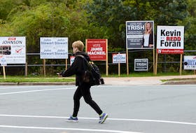 FOR CAMPBELL STORY: A pedestrian crosses Cumberland Drive, backdropped by an array of signs for some of the candidates running in District 4, in Cole Harbour Wednesday October 7, 2020.  TIM KROCHAK PHOTO