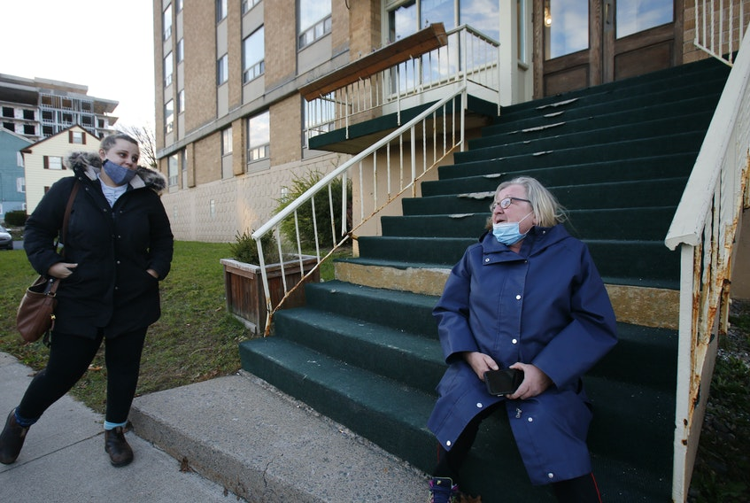 FOR LAMBIE STORY: A passer-by stops to give Grace Fogarty, right, some encouragement as she sits outside her Dutch Village Road apartment building in Halifax Wednesday October 28, 2020. She recently received a $650 rent increase and the woman had seen Fogarty's plight on a social media post and said how angry at how a building owner could just do that.  TIM KROCHAK PHOTO
