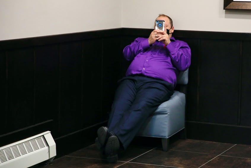 Halifax Regional Police Const. Steve Logan shields his face with his phone during a break in proceedings of a Nova Scotia Human Rights Commission board of inquiry, at a Halifax hotel on Thursday, Nov. 5, 2020.  A man believes police targeted and discriminated against him because of his race.
