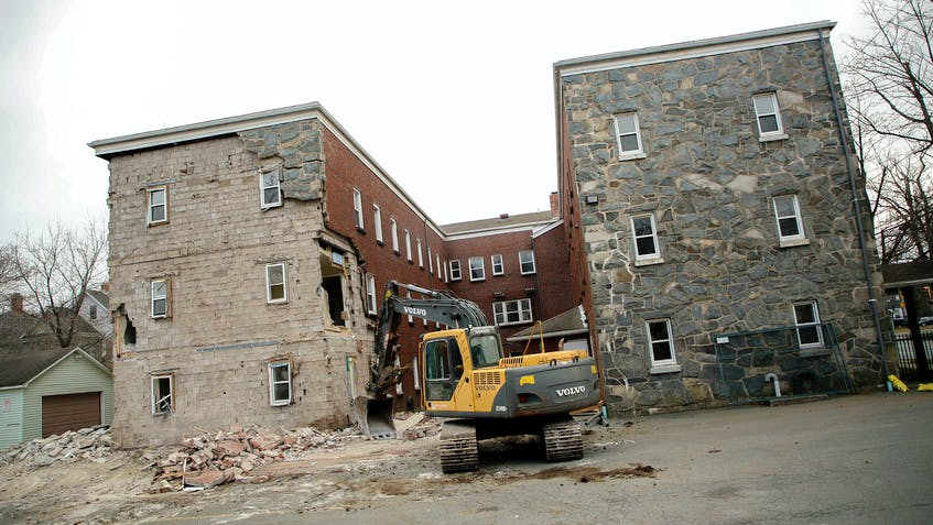 An excavator tears away at Ardmore Hall apartment building Dec. 20, 2020, despite a resident still living on the premises on Oxford and North streets in Halifax. - Tim Krochak