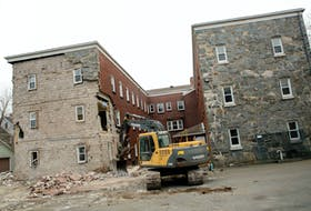 An excavator tears away at Ardmore Hall apartment building Friday despite a resident still living on the premises on Oxford and North Streets in Halifax.