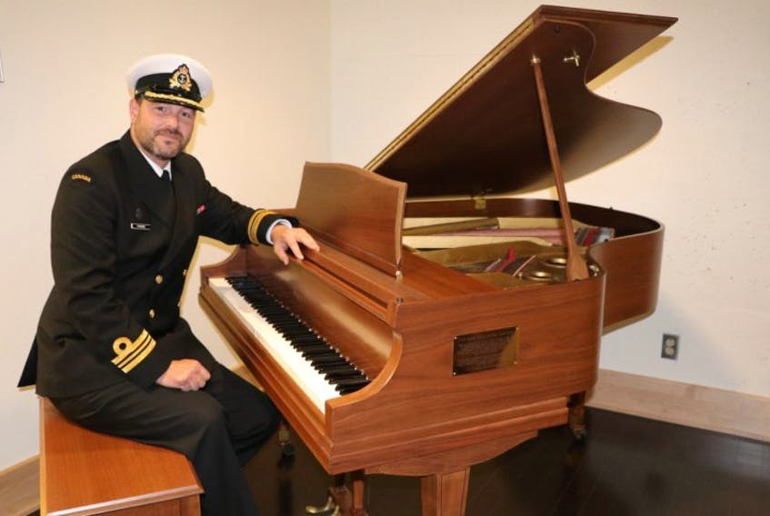 CFS St. John's commanding officer Lt. Cmdr. Gerry Parsons sits at a historic and restored Wurlitzur baby grand piano in the Argentia Room at the St. John's base.
