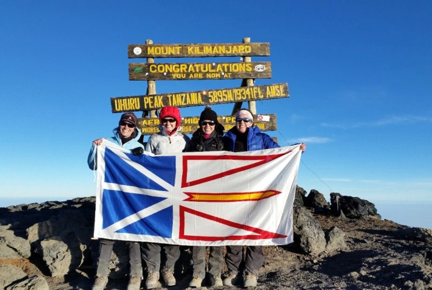Sisters (from left) Mabel Nash, Lisa McGrath, Laurie McGrath and Jacinta McGrath hold the provincial flag at the summit of Mount Kilimanjaro in Tanzania.