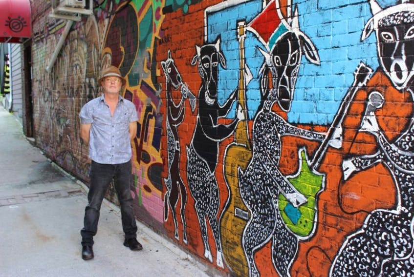 Artist Frank Barry with the mural he painted in the lane between the Black Sheep and Del Sol.