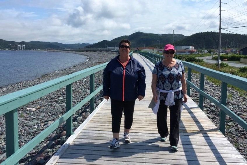 Donna Lambe (left) and Gail Ryan like to walk the boardwalk on the Placentia waterfront on a fine day. Both women recall past flooding in the community before protections such as the boardwalk and breakwater, and say sea level rise is not currently much of a concern.