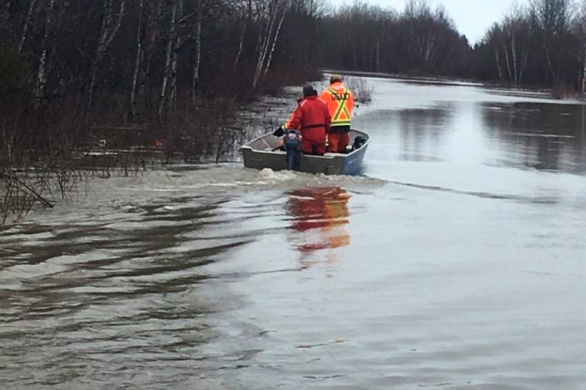 Members of a search and rescue team travel by boat on Mud Lake Road toward the boat launch area as they check on people in the flooded town following the evacuation. - Contributed