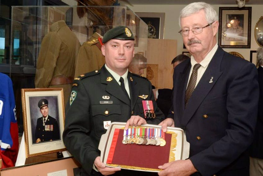 Maj. Kyle Strong (left), deputy commanding officer of the Royal Newfoundland Regiment, First Battalion, accepts the service medals from Fraser Eaton, son of Lt.-Col. Cam Eaton (who is pictured in framed photograph).