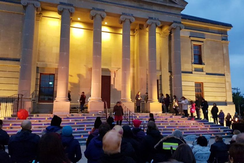 Women and men read the names and biographical details of the 117 missing and murdered Newfoundland and Labrador women and girls during a vigil Wednesday at the Colonial Building in Bannerman Park.