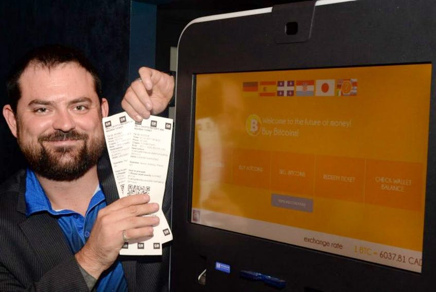 Ray Bursey, CEO of Ghost Technologies, displays cash redeemer vouchers for the shown Bitcoins machine at the Fifth Ticket restaurant/bar on Water Street in St. John's on Thursday evening.