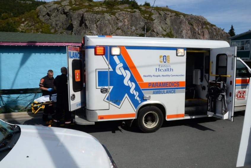 Paramedics set up a stretcher after a man who fell overboard from a small boat Saturday afternoon was to be taken by ambulance to be checked out . His injuries were not considered life threatening.