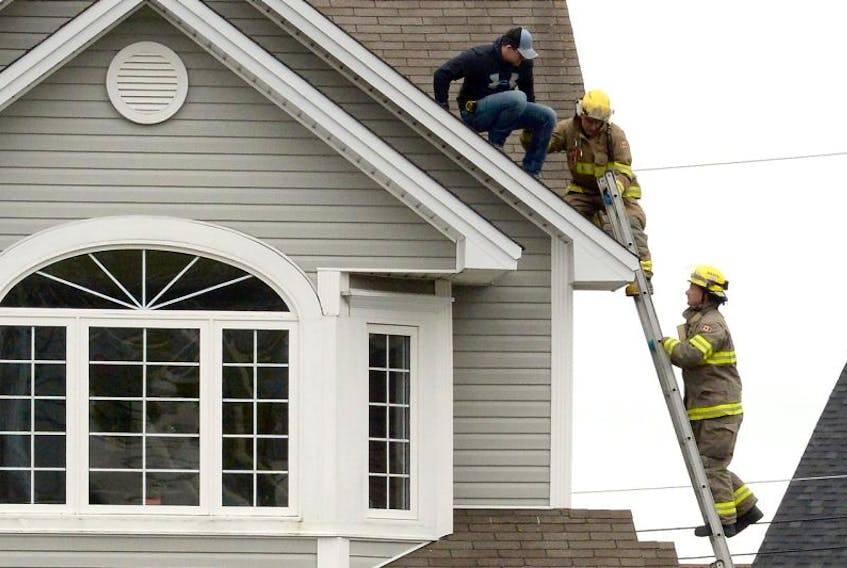 Firefighters help a man from a roof in Mount Pearl Saturday afternoon after his co-worker fell two storeys.