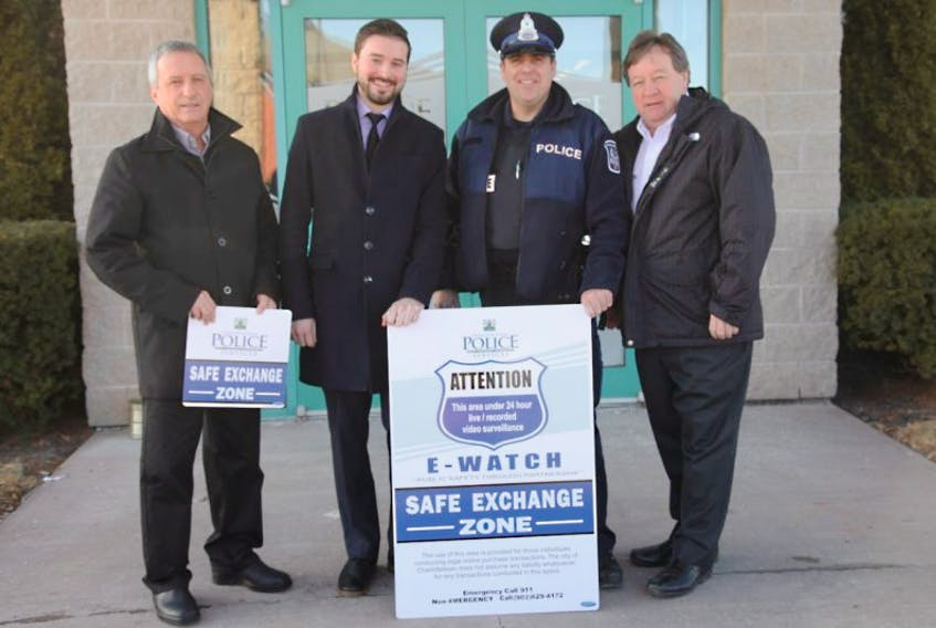 From left, Coun. Kevin Ramsay, chair of the Charlottetown Youth Retention Advisory Board; Zac Murphy, member of the Youth Retention Advisory Board; Const. Trevor Monaghan, Charlottetown Police Services; and Charlottetown Mayor Clifford Lee pose with the signage for eWatch Safe Exchange Zone.