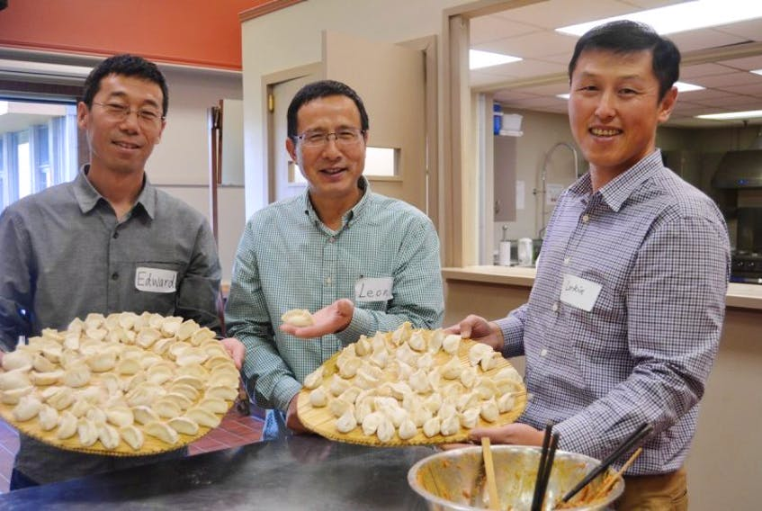 Edward Wang, left, Leon Liang and Larkin Lin, right, show the work of Chinese community members who donated their time and talents to make dumplings and mooncakes for the Chinese Lunar Festival that was attended by Rotarians and their partners. The event was held at the Farm Centre recently.