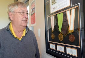 Bill McKinnon looks at his medals on display at the track clubhouse at UPEI Alumni Canada Games Place. They include the first medal won by an Island athlete at the Canada Games.