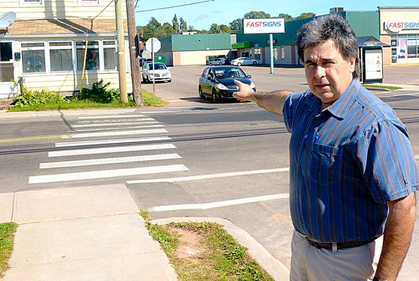 """Coun. Mitch Tweel points to an intersection he describes as a """"death trap"""" at Queen and Pond streets in Charlottetown. Tweel is calling on council to adopt a number of recommendations made in a 2010 report, which recommends moving or relocating the house on the corner. The house extends past the Pond Street stop sign, giving drivers no visibility unless they extend past the sign."""