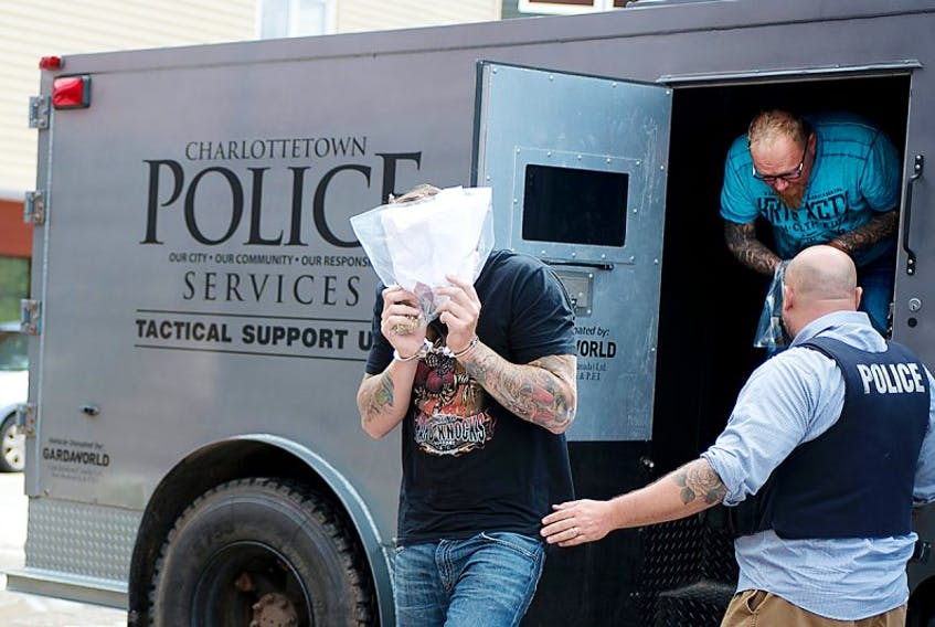 Some of the nine men arrested by police in Charlottetown and are said to be associated with the Hells Angels are escorted into the provincial court in this file photo.