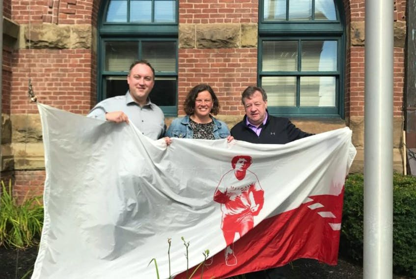 The Terry Fox flag was recently raised at City Hall in Charlottetown by run organizers John Connolly, left, and Sue Connolly, and Mayor Clifford Lee.