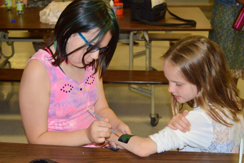 Madelyn Affleck, left, paints a turtle tattoo on the arm of Brooklyn Pirch at Mount Stewart Consolidated School on Friday. The school and Mi'kmaq Confederacy of P.E.I. were marking the National Day of Healing and Reconciliation. Pirch was also sporting a tattoo on her cheek of an eagle. The turtle and eagle are two of the seven sacred Mi'kmaq teachings.