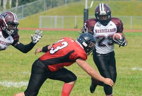 Holland College Hurricanes receiver Samuel Valerie uses the stiff arm to elude the tackle of UNB Red Bombers defensive back Coel Storey Saturday during Atlantic Football League action at UPEI Alumni Canada Games Place MacAdam Field.