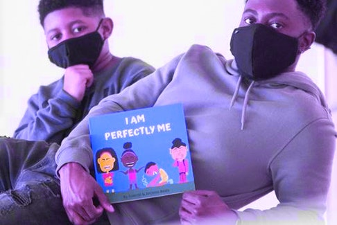 Keonte Beals and his younger brother Antonio display their book I Am Perfectly Me. Hassan E. Almusawii