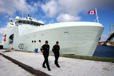 Cmdr. Corey Gleason, left, commanding officer of HMCS Harry DeWolf, and Chief Petty Officer First Class Jamie Haas walk alongside the ship at the Halifax Dockyard on Oct. 23, 2020. TIM KROCHAK PHOTO